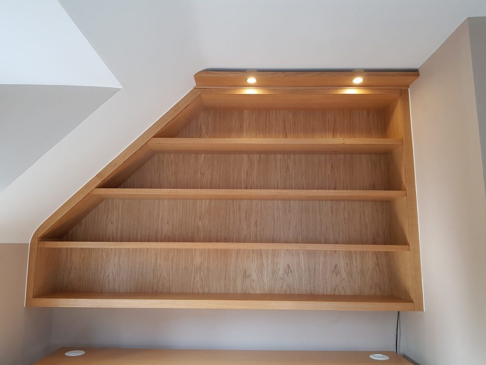 Bespoke bookshelf with integrated lighting maximises the use of the space under a sloped ceiling