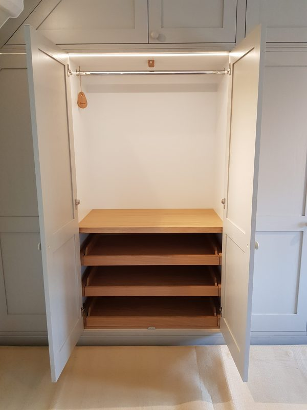 Three internal shoe trays sit below short height hanging space