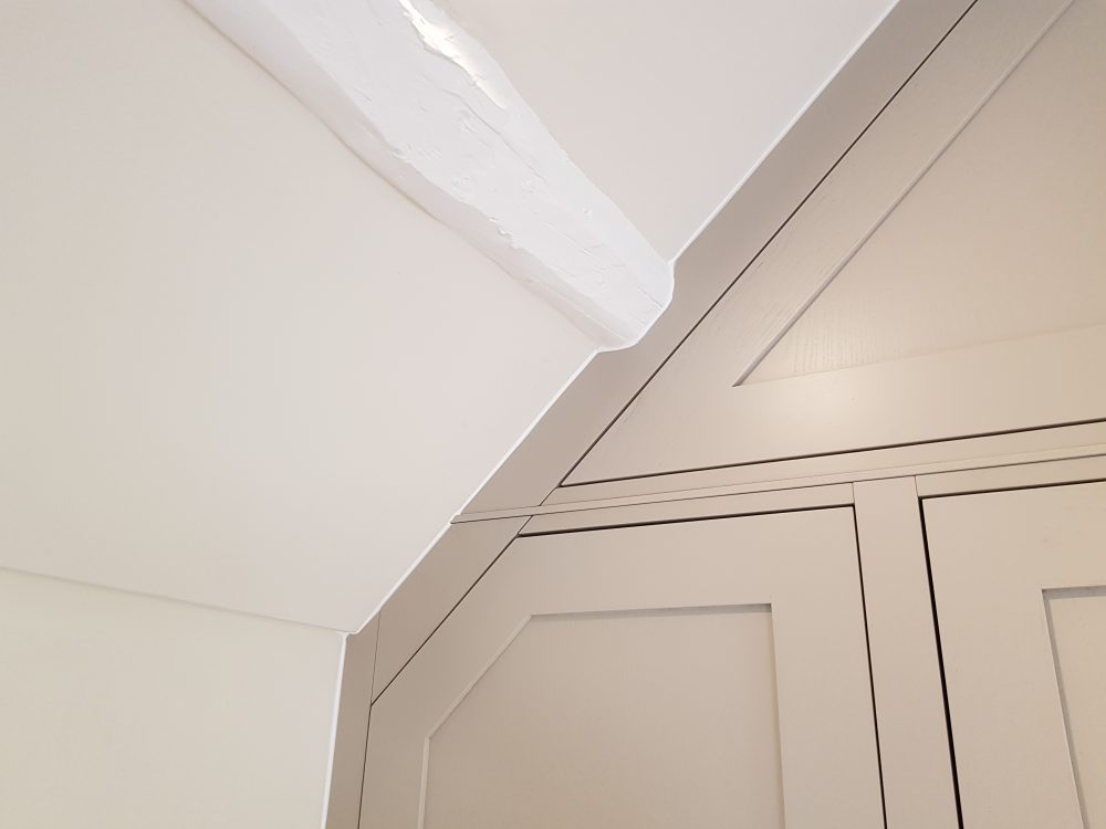 Cabinetry scribed to fit perfectly to the angled ceiling and feature beams