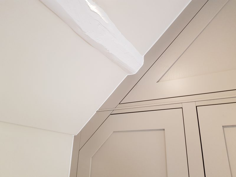 Cabinetry scribed to fit perfectly to the angled ceiling and feature beams.